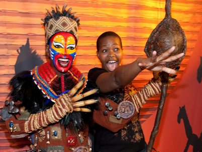 Buyi Zama stands next to the wax figure of the Rafiki character